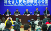 """Five people sitting on a panel in front of an audience. The wall behind them reads """"Information Office of Hubei Provincial People's Government."""""""