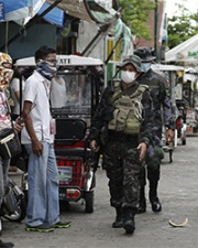 Military personnel walk past Philippines citizens