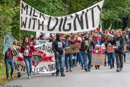 """Members of Migrant Justice march holding signs that read """"Milk with Dignity"""""""