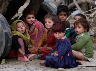 """Afghan refugee girls sit behind a wooden cart in a slum in Pakistan. (AP  Photo/Muhammed Muheisen"