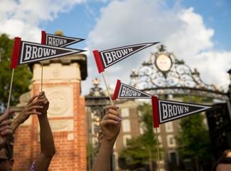People raise Brown University pendants in the air