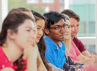 Students listen intently to a speaker