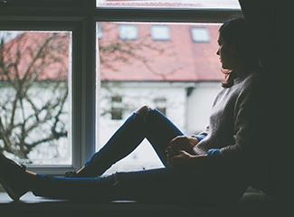 A woman looks out a window