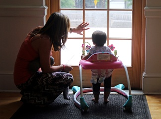 A woman and her baby look out the window