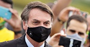Bolsanaro with a black face mask on and people standing behind him filming with cell phones