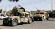 Two Taliban military trucks drive down the street