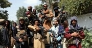 A group of Taliban fighters stand together, raising their guns and looking at the camera.