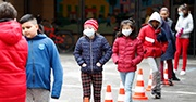 Children wearing masks and walking into school while socially distancing