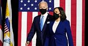 Biden and Harris walk together, both wearing masks