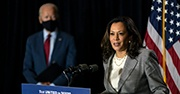 Kamala Harris speaks at a podium while Joe Biden watches in the background