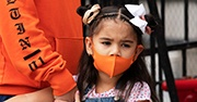 A small child wears an orange mask while holding her parent's hand