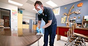 A man wearing a face shield cleans a desk inside a classroom