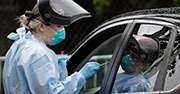 A woman wearing protective gear gives a Covid test through a car window