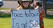 "Woman wearing a mask and holding up a sign that says ""Face to face is not safe"""