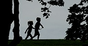 The shadows of two small children running and playing outside