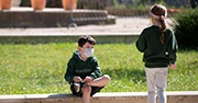 Two children stand near each other, talking with face masks on