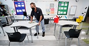 Man wearing a mask cleaning the desks at a school