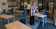 A teacher measures 6 feet between desks in a classroom