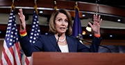 Nancy Pelosi stands at a podium, speaking with her hands raised in the air