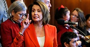 Nancy Pelosi points a finger while talking, she wears a red blazer