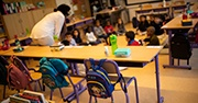 A classroom with spaced out chairs and backpacks, children sit on the rug