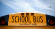 A cropped photo of the top of a school bus with the sky in the background