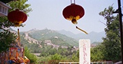 The Great Wall of China in the background of the image with two red lanterns hanging in the forefront