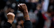 Two fists are raised in the air as a sign of protest, the background is blurred