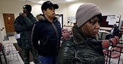 Three people wait in line to receive food stamps