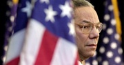Colin Powell stands behind an American flag - he is in focus and the flag is blurry