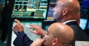 Two men looking at screens displaying stock information