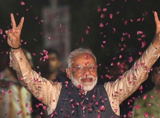 Modi gesturing the peace sign in both hands above his head as he walks through confetti