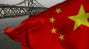 China's flag blowing in front of a bridge