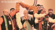 Indian leaders honoring Modi by placing a flower garland over him