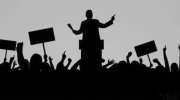 silhouette of a man at a podium speaker to a crowd