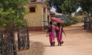 two Anganwadi workers in pink sarees and pink umbrellas