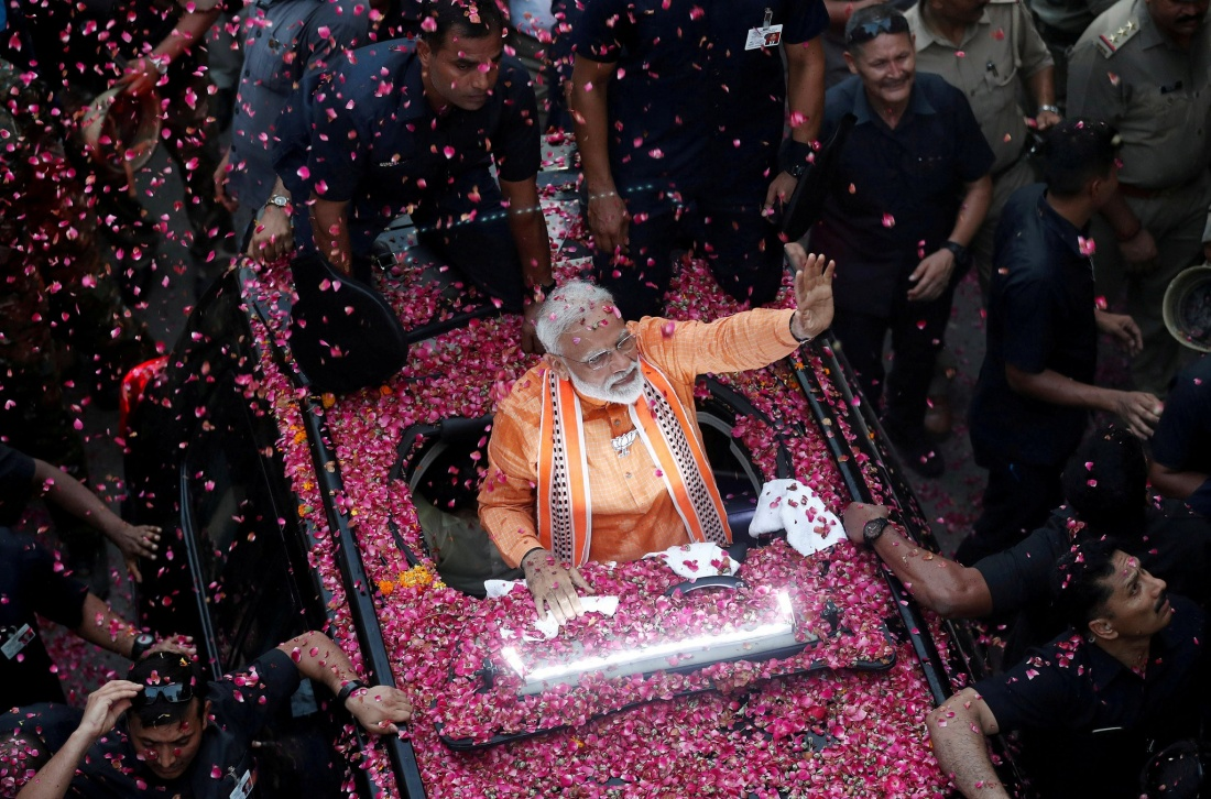Modi dressed in orange riding on a car covered with pink rose petals